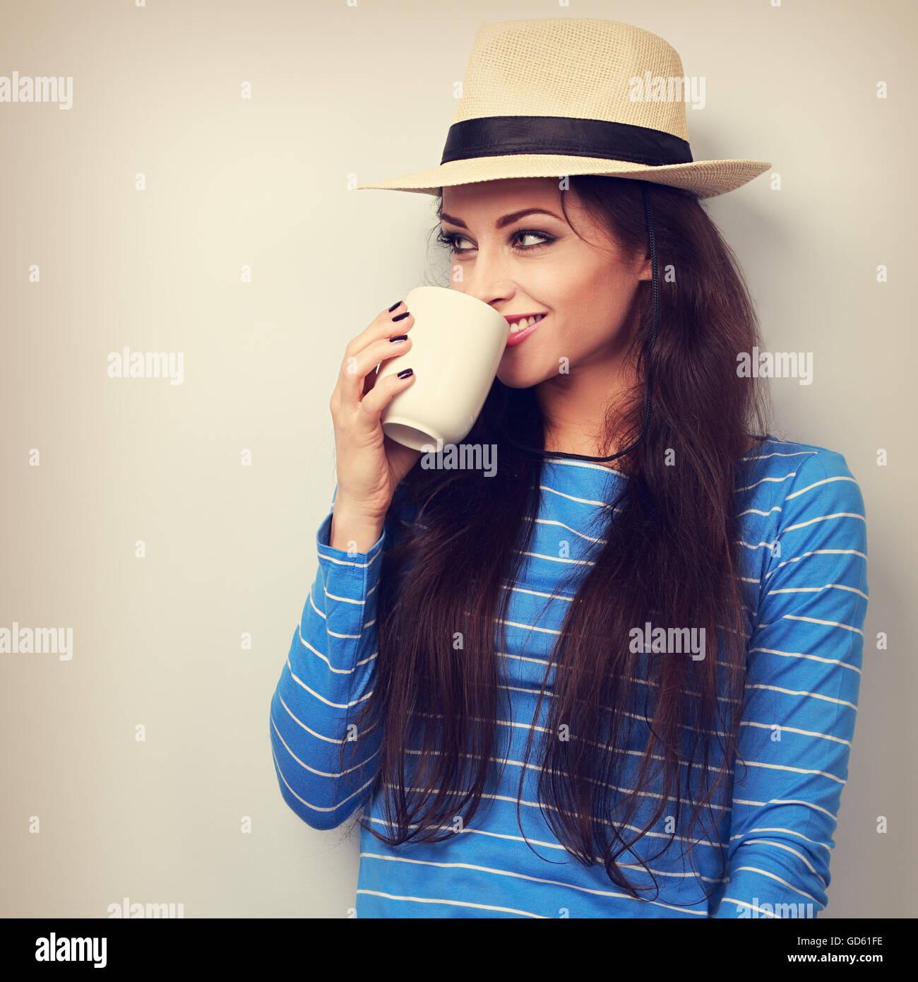 Carino felice donna informale nel cappello di paglia tenendo in mano tazza di tè e guardando. Tonica closeup Immagini Stock