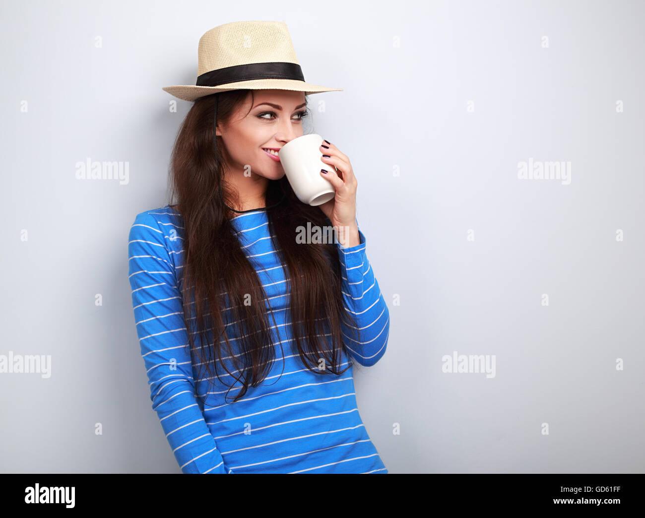 Carino felice donna informale nel cappello di paglia tenendo in mano tazza di tè e guardando su sfondo blu Immagini Stock