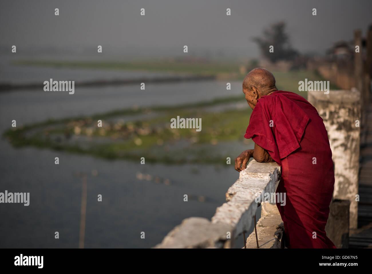 Un anziano monaco buddista contemplando il lago Taungthaman, Amarapura, Myanmar. Immagini Stock