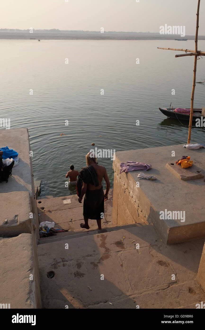 Un uomo che fa un passo verso il basso per fare il bagno nel fiume sacro Gange poco dopo l'alba. Varanasi, Uttar Immagini Stock
