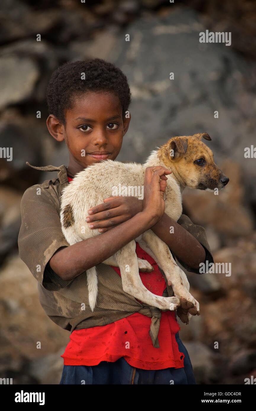 Ragazzo etiope holding timida di cane. La strada per sbarcare, Etiopia. Immagini Stock
