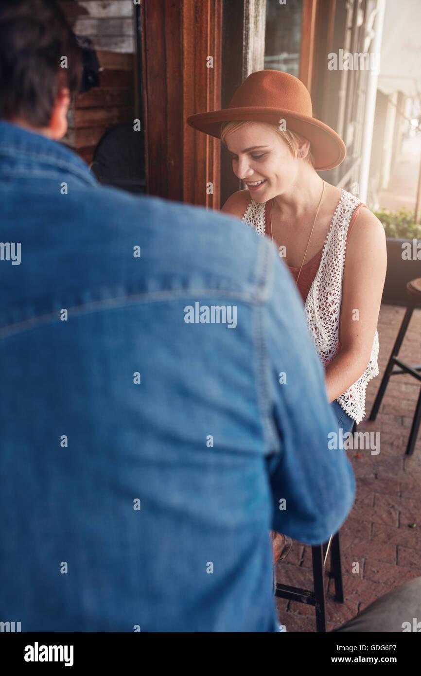 Giovane donna caucasica indossando hat seduto a un coffee shop con il suo amico maschio. Giovani amici seduti ad Immagini Stock