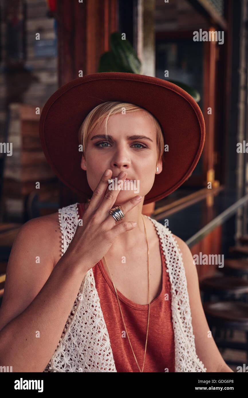Ritratto di giovane donna con cappello di fumare una sigaretta in una caffetteria. Immagini Stock