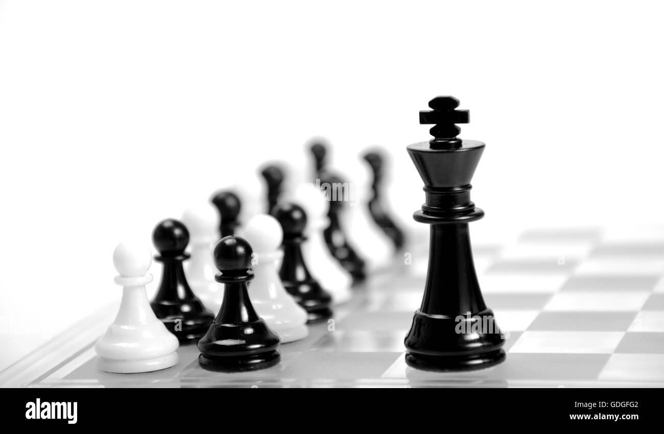 Il bianco e il re nero sulla scacchiera opposti l'uno all'altro,in bianco e nero di pedine in background. Immagini Stock
