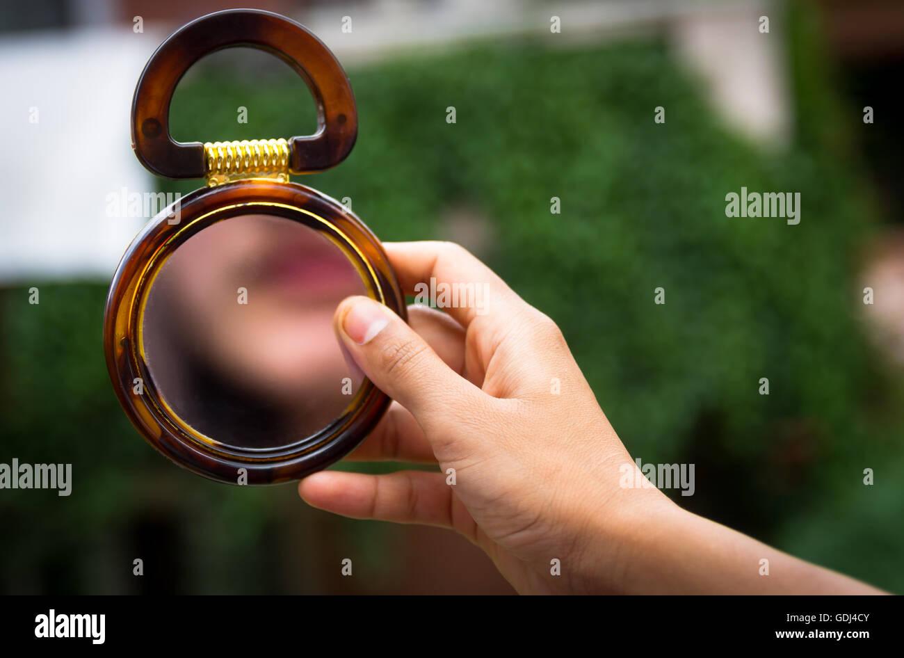 Una ragazza sta guardando lo specchio con tenendolo con la mano. Immagini Stock