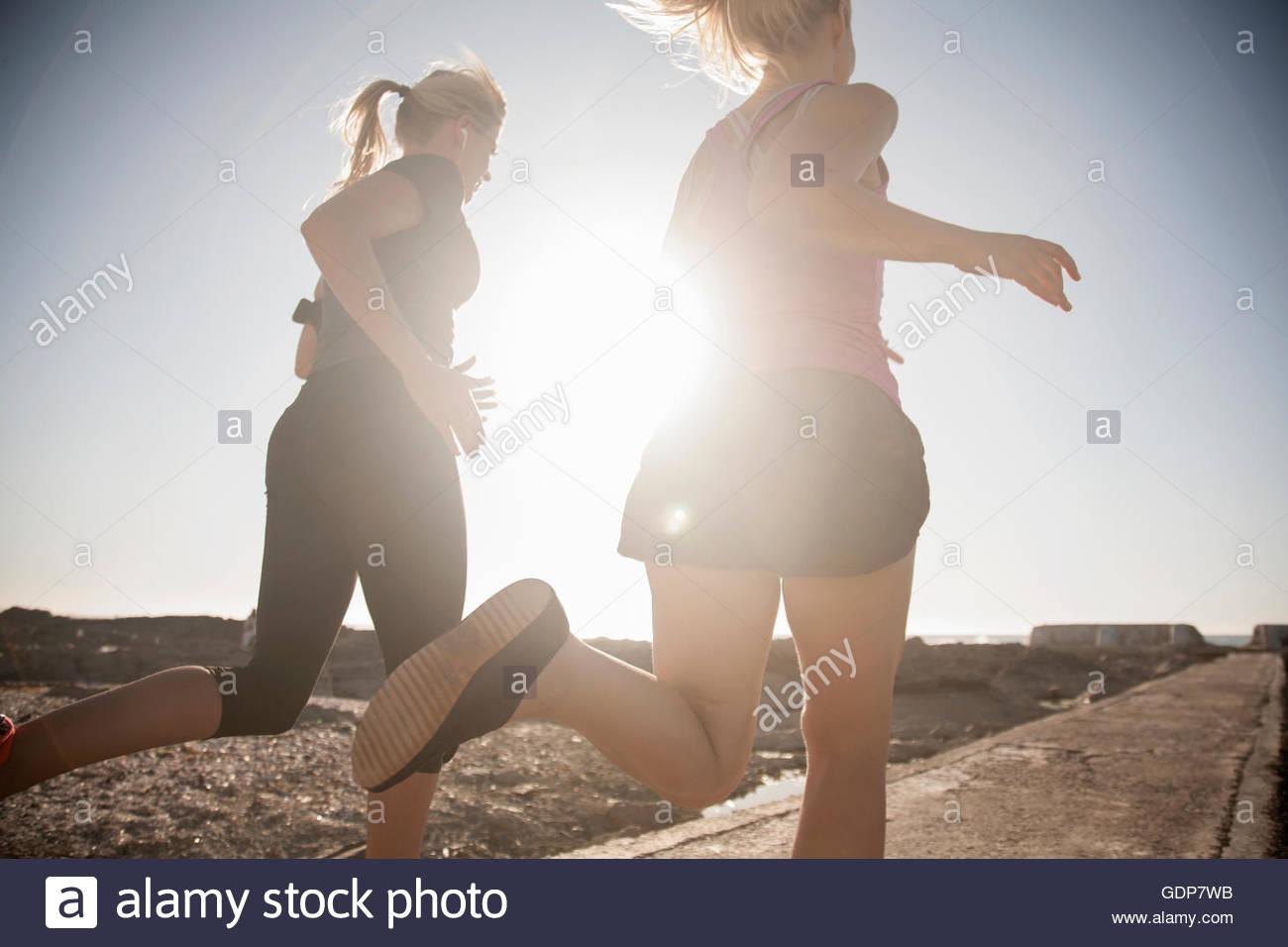 Due giovani donne che corre lungo la costa soleggiata, Seapoint, Cape Town, Sud Africa Immagini Stock