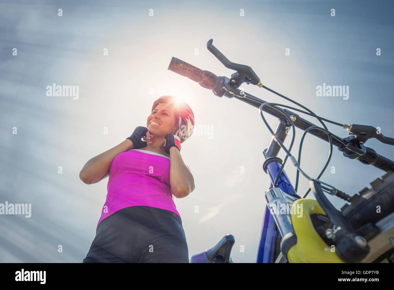 Donna con mountain bike mettendo il suo casco su, Canton Vallese, Svizzera Immagini Stock