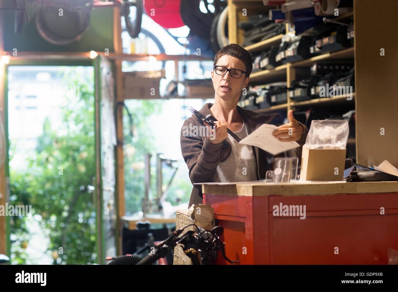 Donna al contatore in officina biciclette azienda parte bici e documenti Immagini Stock