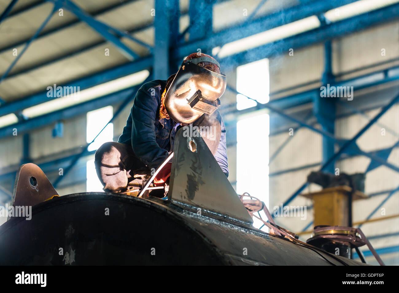 Saldatrice a lavorare in un ambiente industriale di fabbricazione di apparecchiature in acciaio Immagini Stock