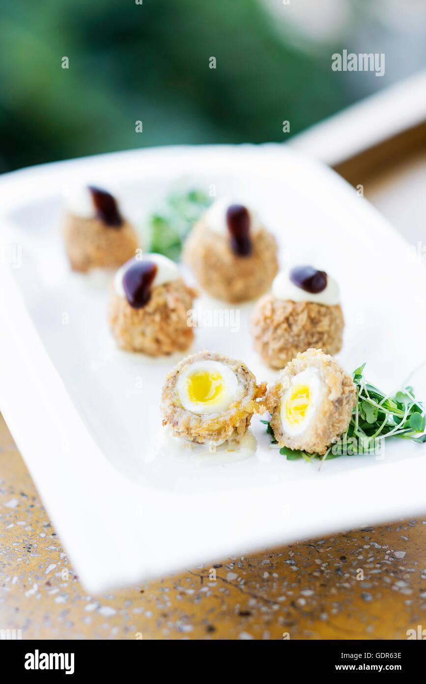 Carne di maiale impanato e uovo di quaglia sofisticato gourmet cucina moderna starter snack alimentare Immagini Stock