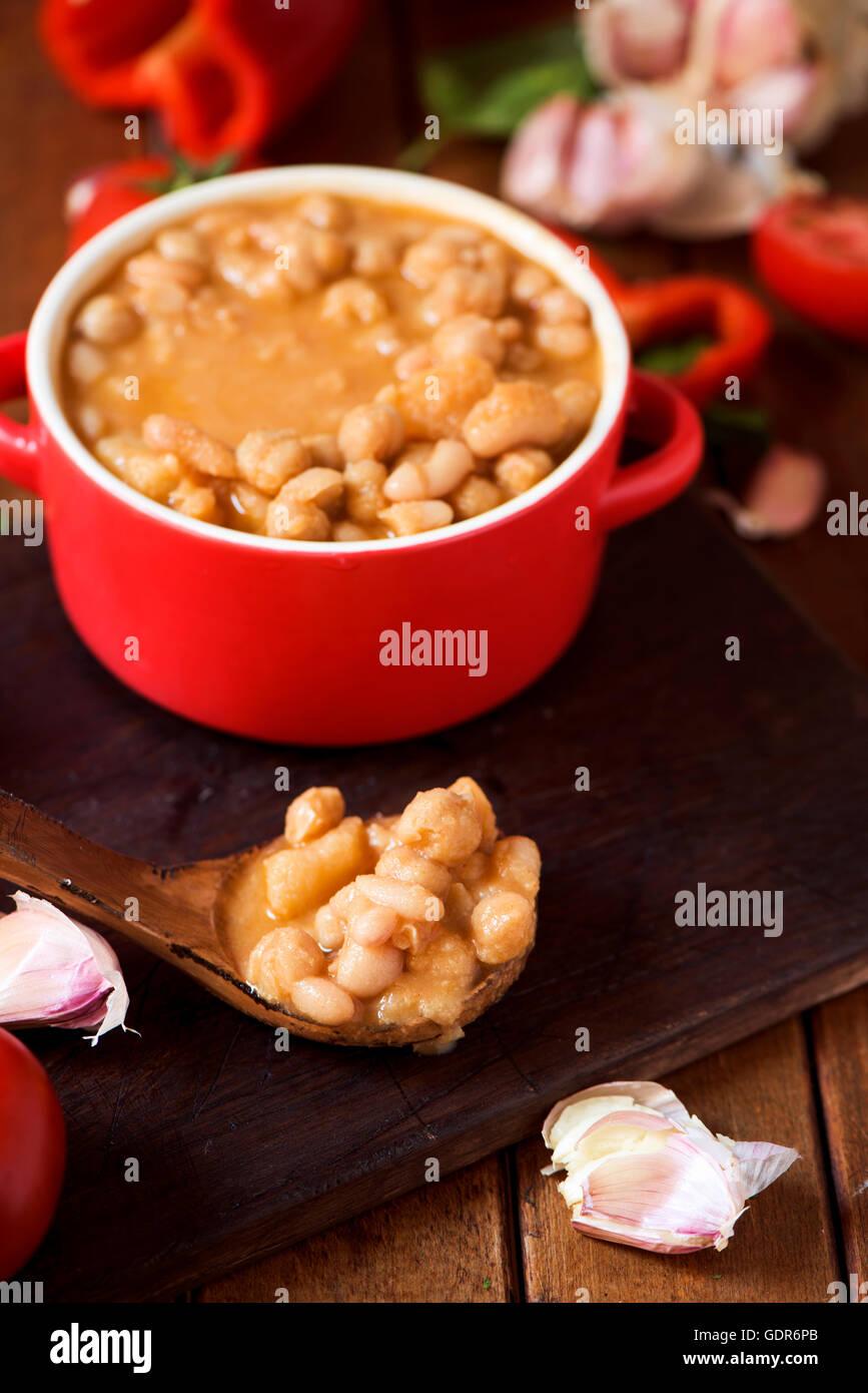 Una casseruola di terracotta con potaje de garbanzos, uno spagnolo spezzatino di ceci e alcune verdure per prepararlo Immagini Stock