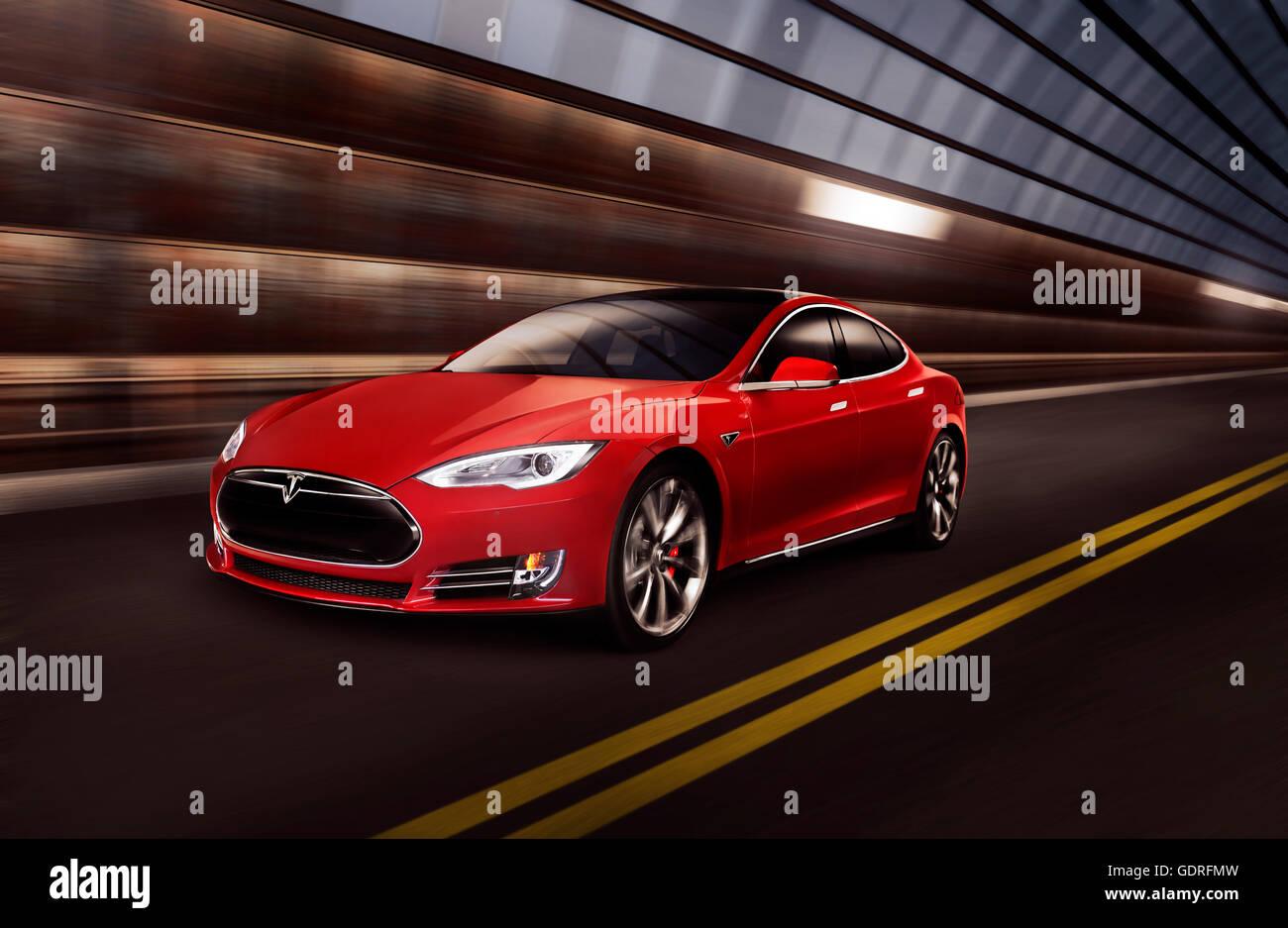 Rosso Modello Tesla S luxury auto elettrica accelerando lungo un metallo tunnel industriali Immagini Stock