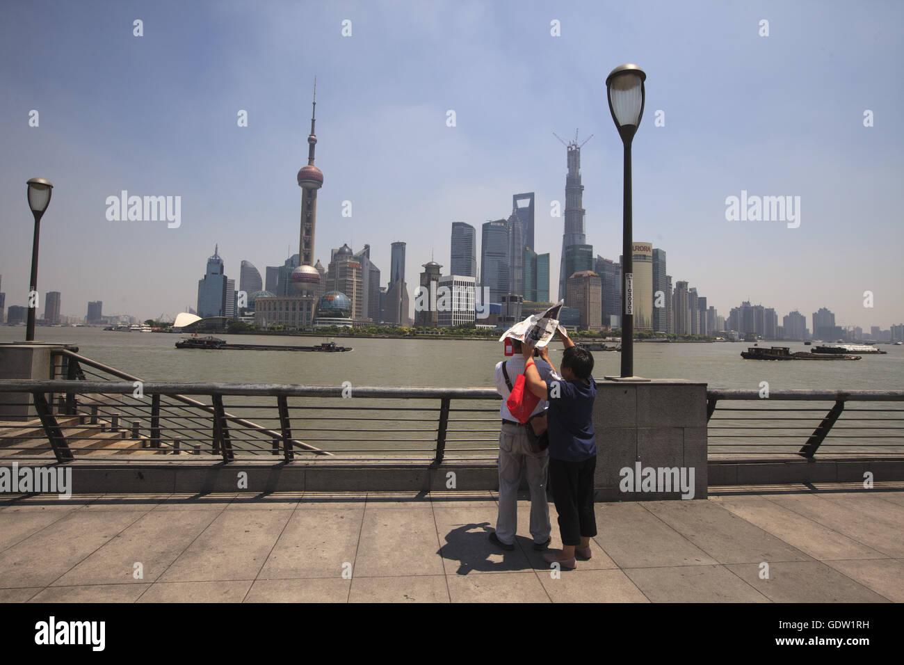 Una donna usa il quotidiano per bloccare la luce solare per un uomo Immagini Stock