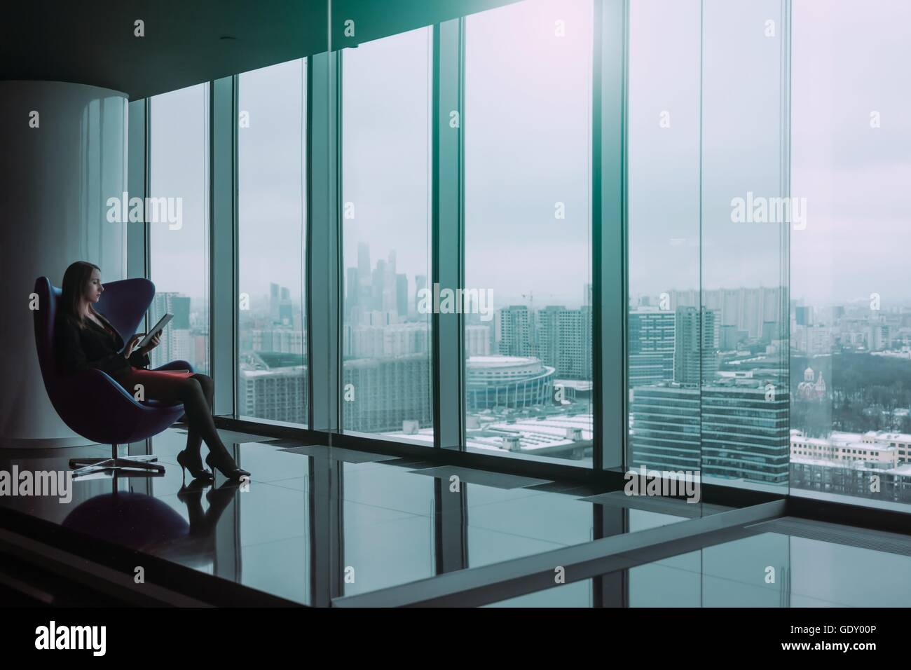 Silhouette di giovane donna di affari con la compressa seduto su una sedia, in inverno il paesaggio della città Immagini Stock