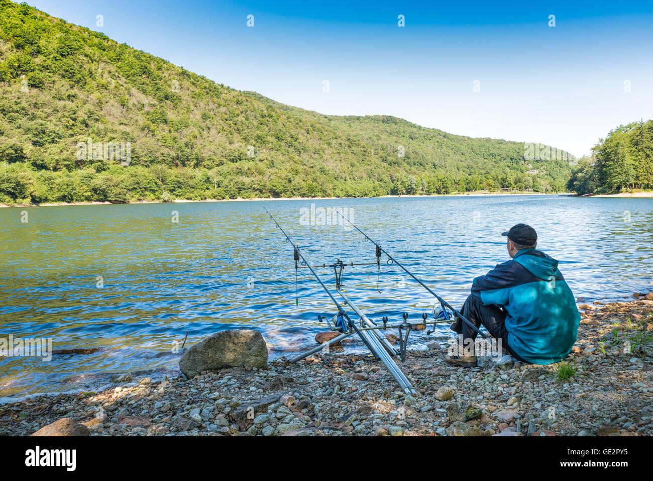 Le avventure di pesca, la pesca alla carpa. Pescatore sulle rive di un lago Immagini Stock