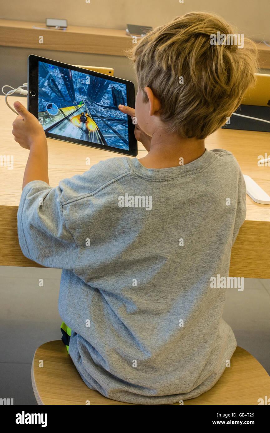 Un giovane ragazzo 7-8 anni gioca un gioco su un iPad all'Apple Store di Santa Barbara in California. Immagini Stock
