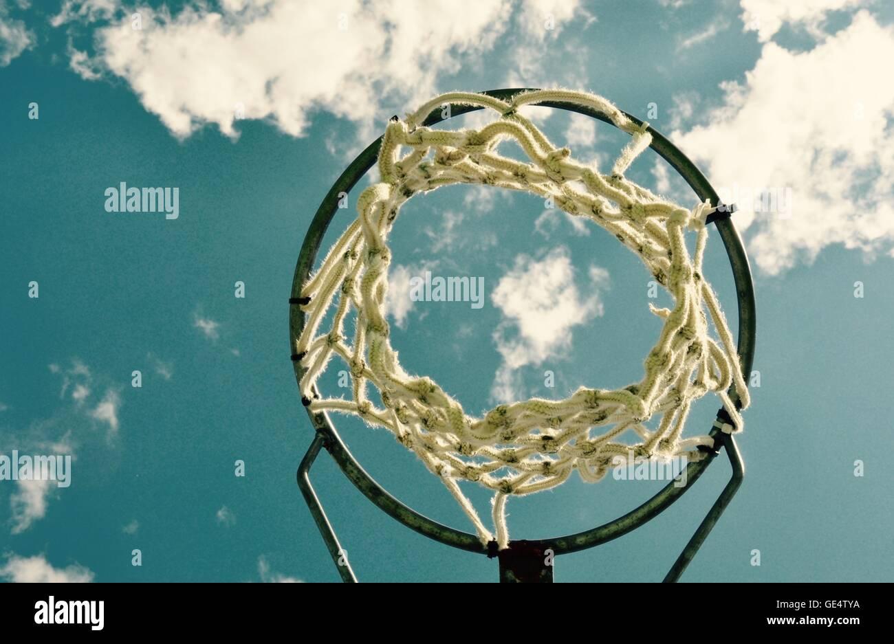 Prospettiva astratta di un cerchio di netball con net contro un cielo blu e Sfondo nuvola. Immagini Stock