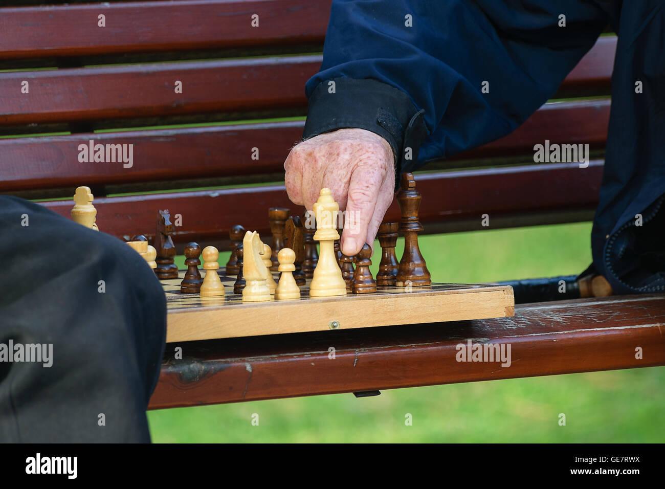 Amici di vecchia data e tempo libero. Due anziani divertirsi e giocare a scacchi gioco al parco sulla panchina. Immagini Stock