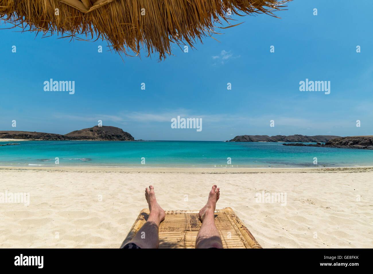 Gambe di guy rilassante sulla spiaggia sotto ombrellone Immagini Stock