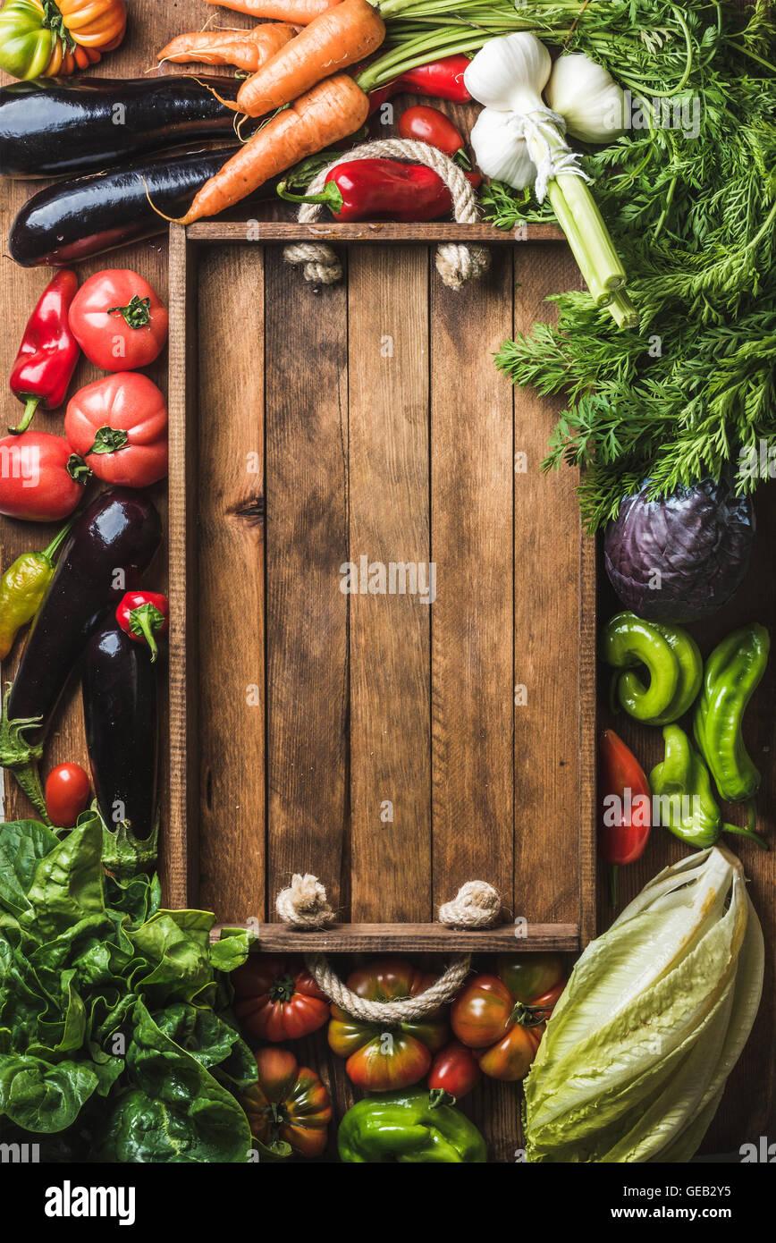 Freschi ingredienti grezzi per la cucina dietetica o insalata rendendo con legno rustico vassoio in centro, vista Immagini Stock