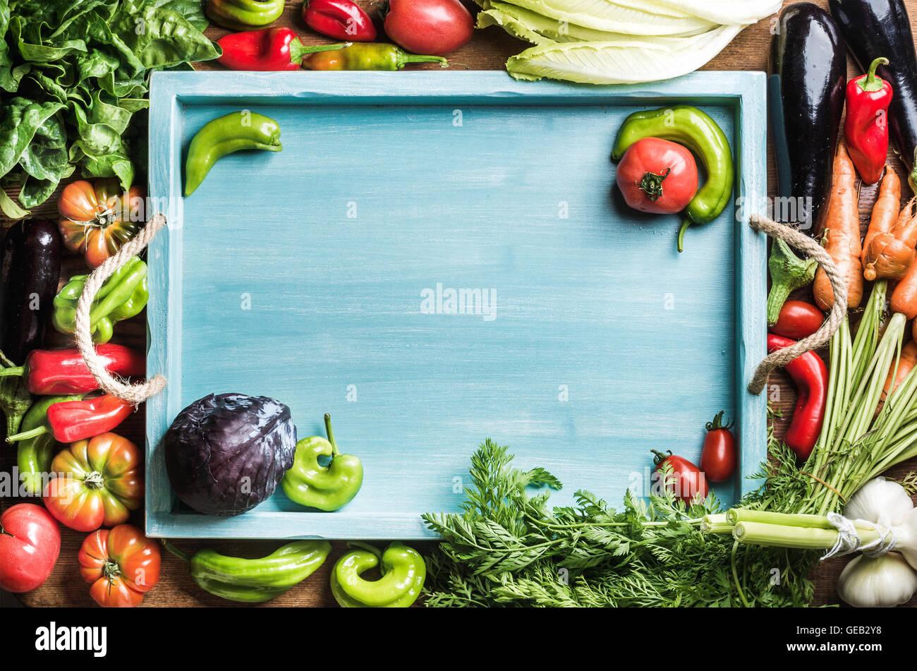 Freschi ingredienti grezzi per la cucina dietetica o insalata rendendo con blu vassoio in legno in centro, vista Immagini Stock