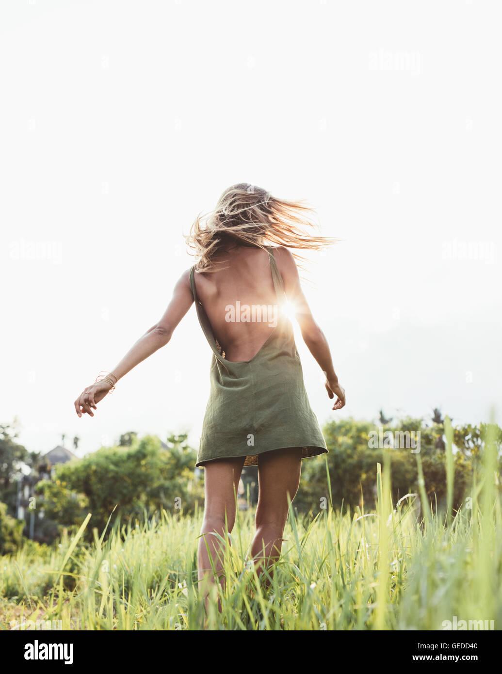 Vista posteriore del colpo di una giovane donna nel campo con sun flare. Bellissima femmina in sundress in un campo Immagini Stock