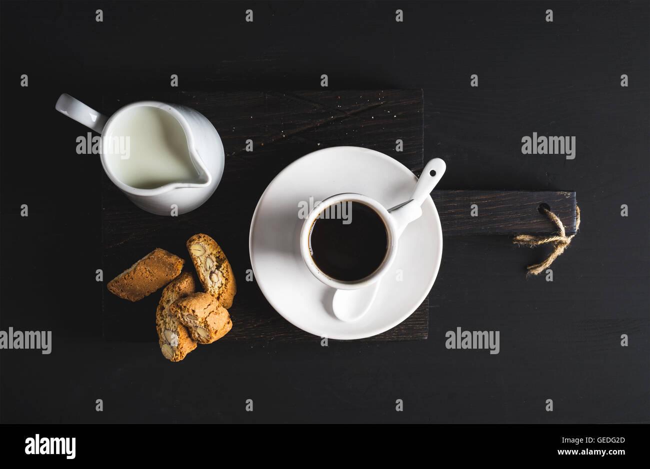 Tazza di caffè caldo, creamer con latte e biscotti sul buio rustico di legno su sfondo nero Immagini Stock