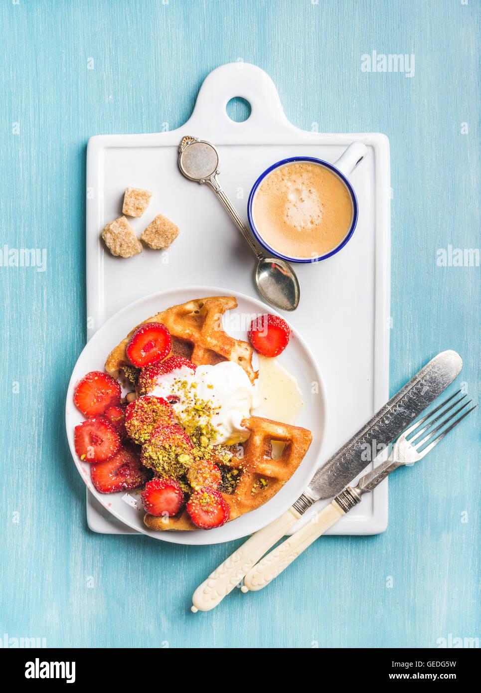 Set colazione. Warm waffles Belgi fatti in casa con panna montata, fragola, sciroppo d'acero, pistacchi tritati, Immagini Stock