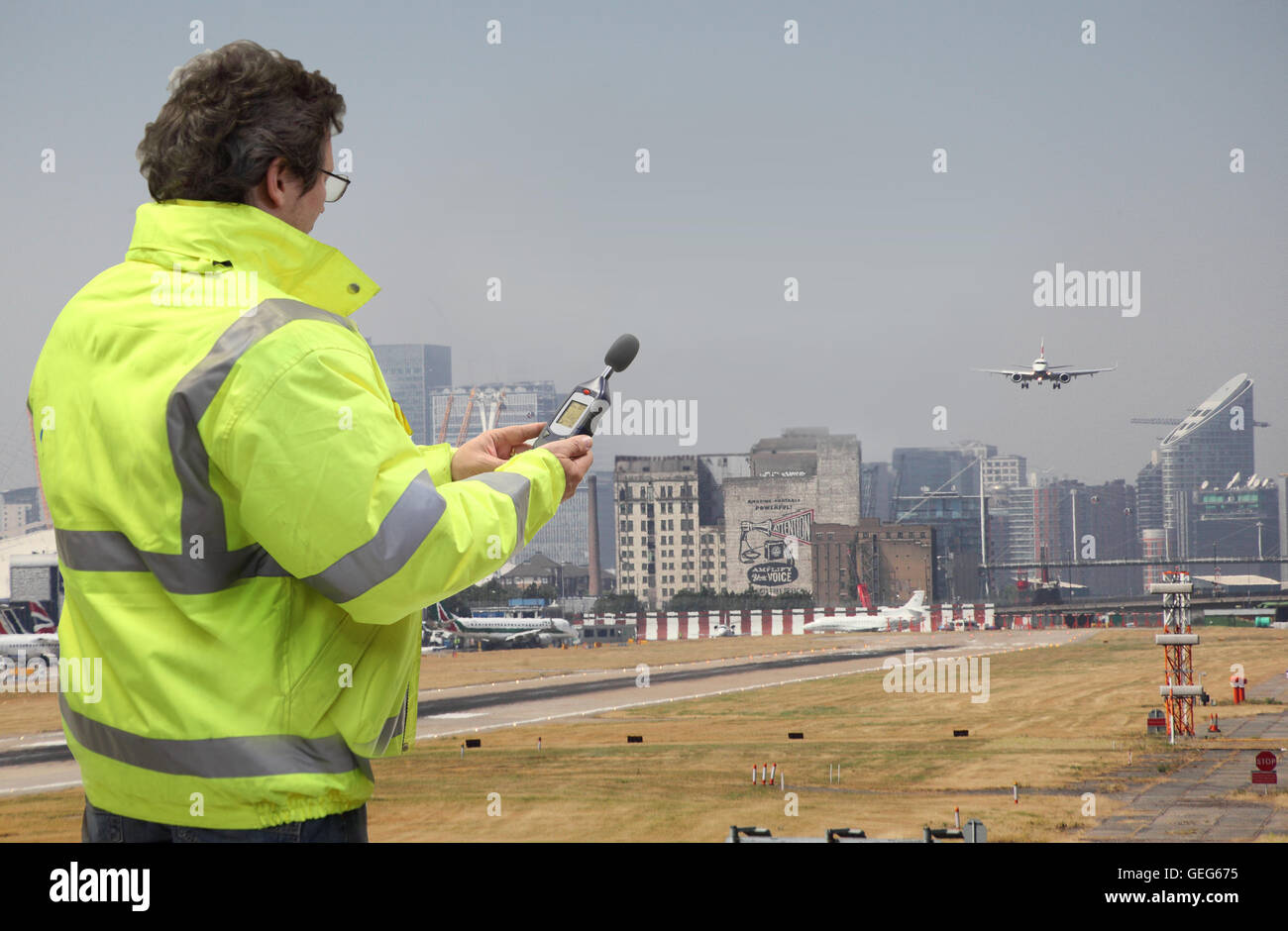 Un ingegnere ambientale controlla i livelli di rumore all'aeroporto di London City come piano terre. canary Immagini Stock