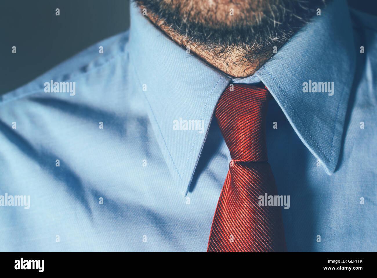 Imprenditore in maglietta blu e rosso cravatta in ufficio con forti ombre, adatto per una intensa attività Immagini Stock