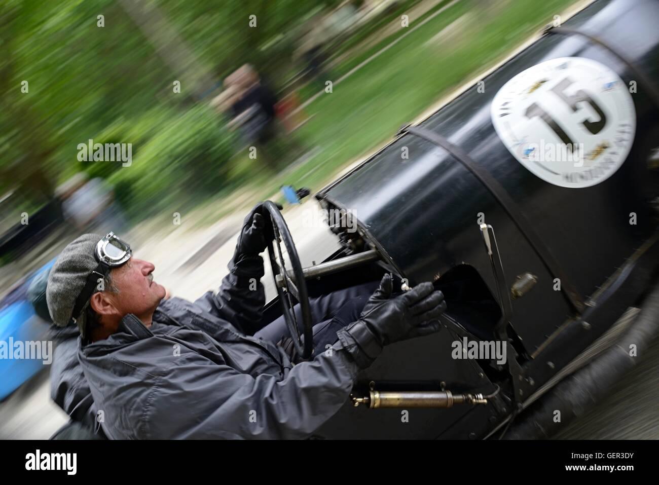 Driver del vintage Bugatti nel periodo meteo ingranaggio su un classico auto da rally, accelerando la distanza dalla Immagini Stock