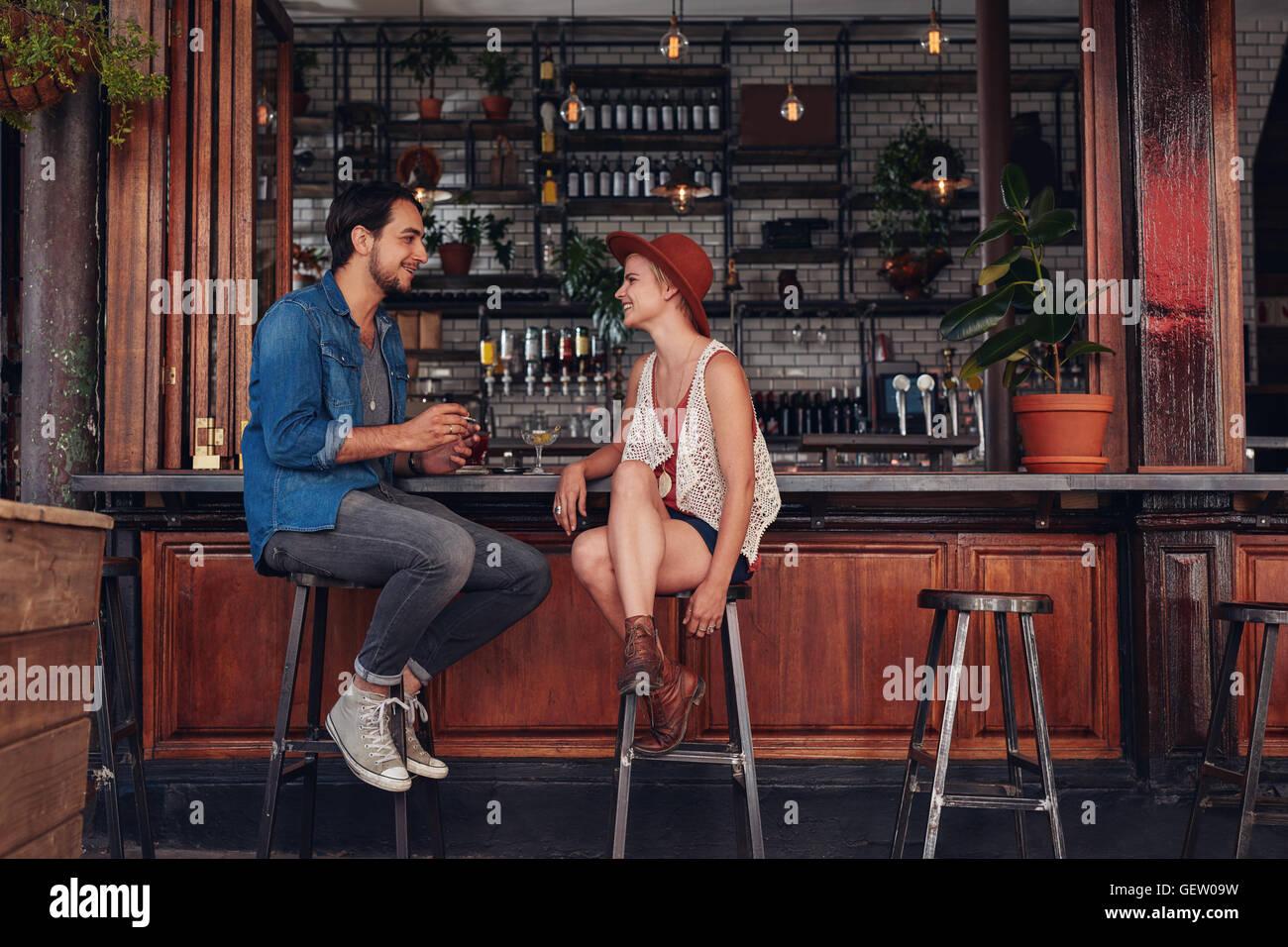 Colpo di coppia giovane seduto presso il cafe contatore. Giovane uomo e donna presso la caffetteria. Immagini Stock