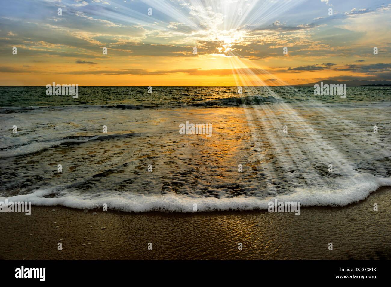 Ocean sunset raggi è un oceano etereo scenic con raggi di sole lo scoppio via dal sole di setting come un onda Immagini Stock