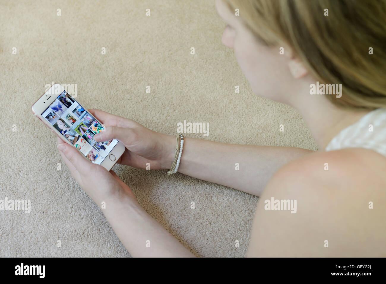 Ragazza adolescente utilizzando Instagram social media app sul suo telefono cellulare (iphone) Immagini Stock