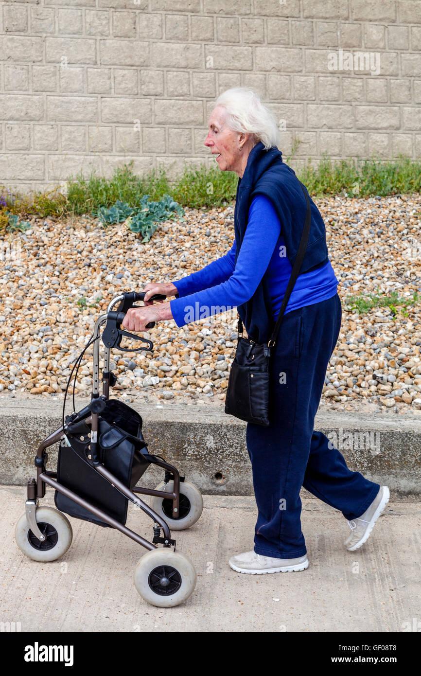 Una donna anziana a piedi con una camminata Rollator Aiuto, Rottingdean, Sussex, Regno Unito Immagini Stock