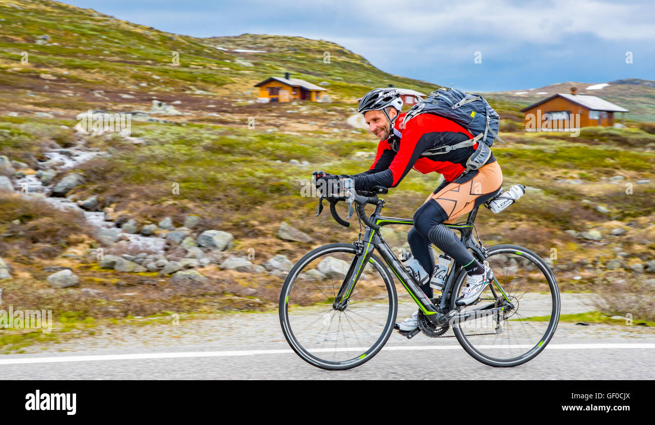 Ciclista pedala sulla Route 7, Parco Nazionale di Hardangervidda in primavera. Norvegia Hordaland, Scandinavia, Immagini Stock