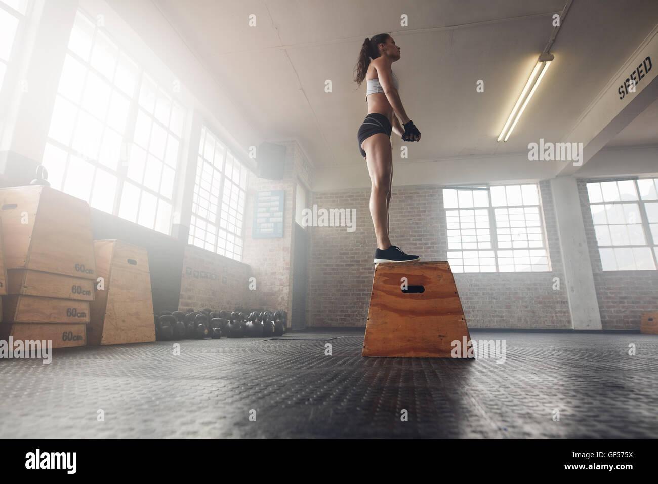 Bassa angolazione di montare i giovani modello femminile in sports wear in piedi su una scatola in palestra. Donna Immagini Stock