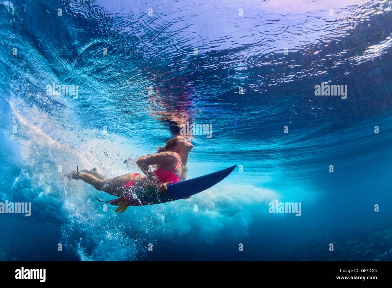 Giovane ragazza attiva indossando un bikini in azione - surfer con tavola da surf subacquea Immersioni sotto il Immagini Stock