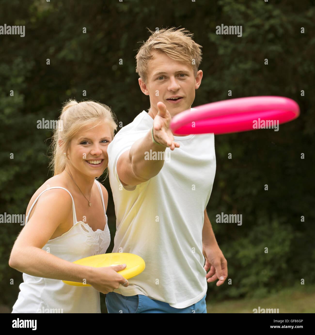 Ritratto di una giovane coppia la riproduzione di un disco di flying game Foto Stock