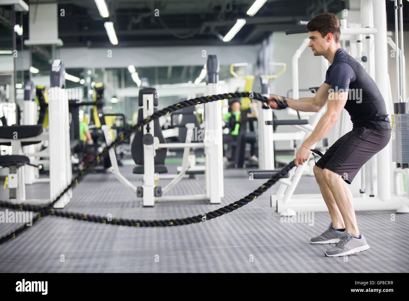 Giovane uomo esercitando con combattendo la corda in palestra Foto Stock
