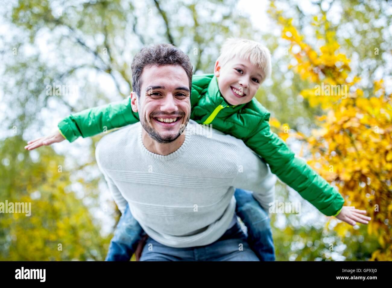 Modello rilasciato. Padre figlio portante sovrapponibile in autunno, sorridente, ritratto. Immagini Stock