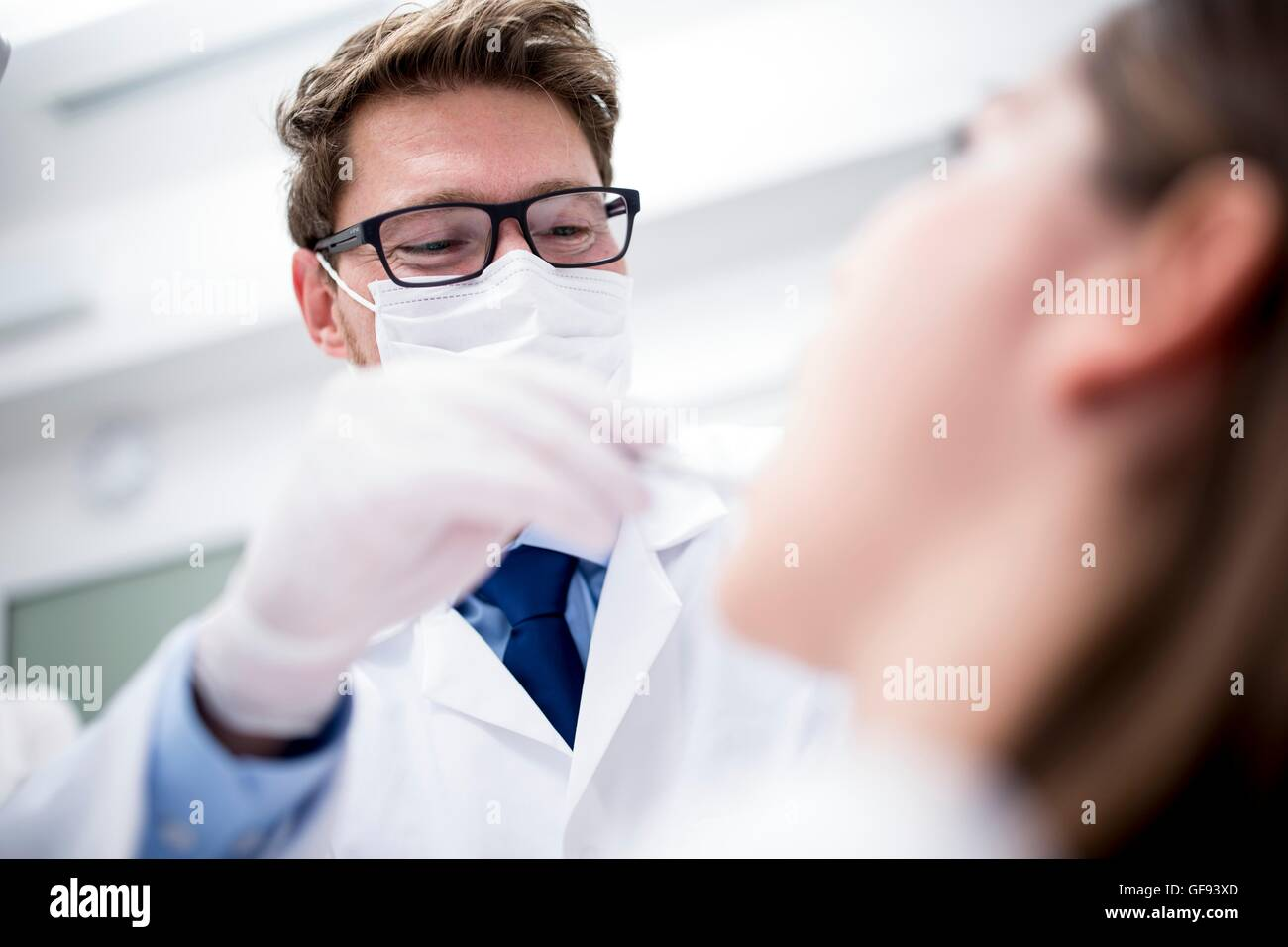 Modello rilasciato. Dentista esaminando denti del paziente in Clinica del dentista. Immagini Stock
