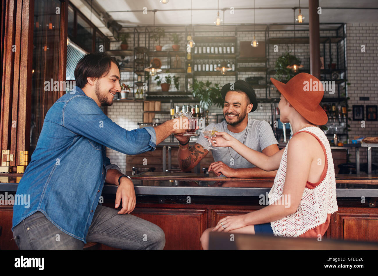 Tre giovani seduti al ristorante e avente un toast. Gruppo di amici in un bar con un drink e tostatura. Immagini Stock