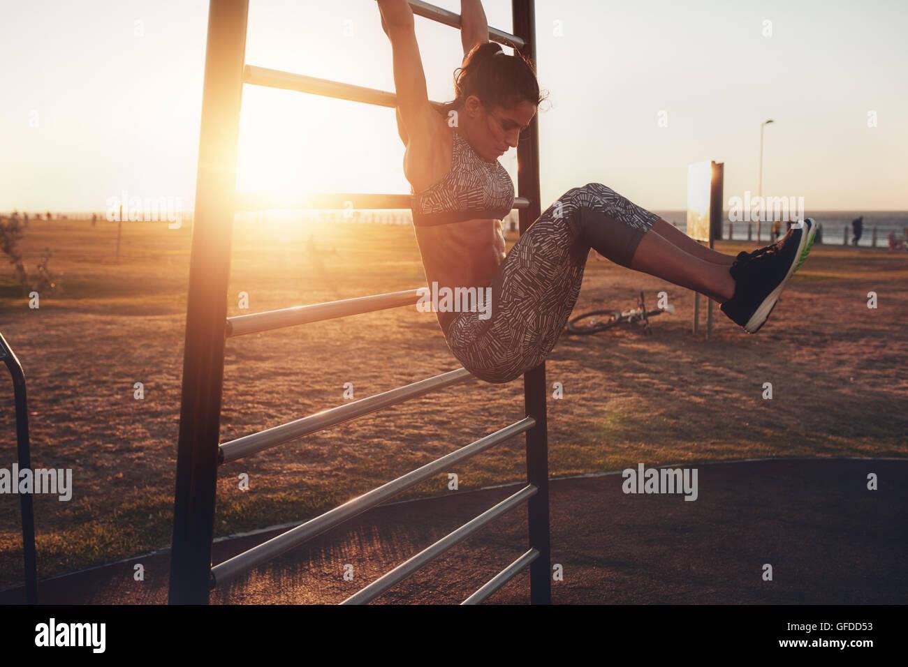 Candide colpo di vero e sano montare donna eseguendo appesi solleva la gamba sul fitness all'aperto dalla stazione Foto Stock