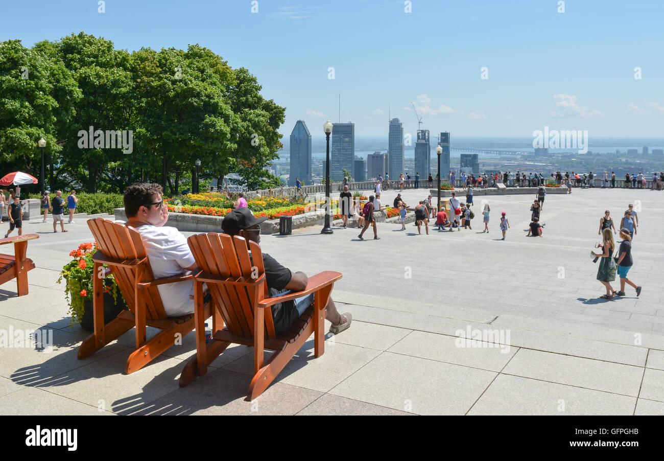 Mount Royal Park Viewpoint, Montreal, Canada - due giovani uomini seduti in sedie di legno per guardare la gente Immagini Stock
