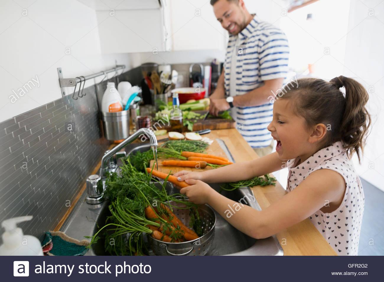 Padre per la cottura e la figlia di carote di lavaggio al lavello da cucina Immagini Stock