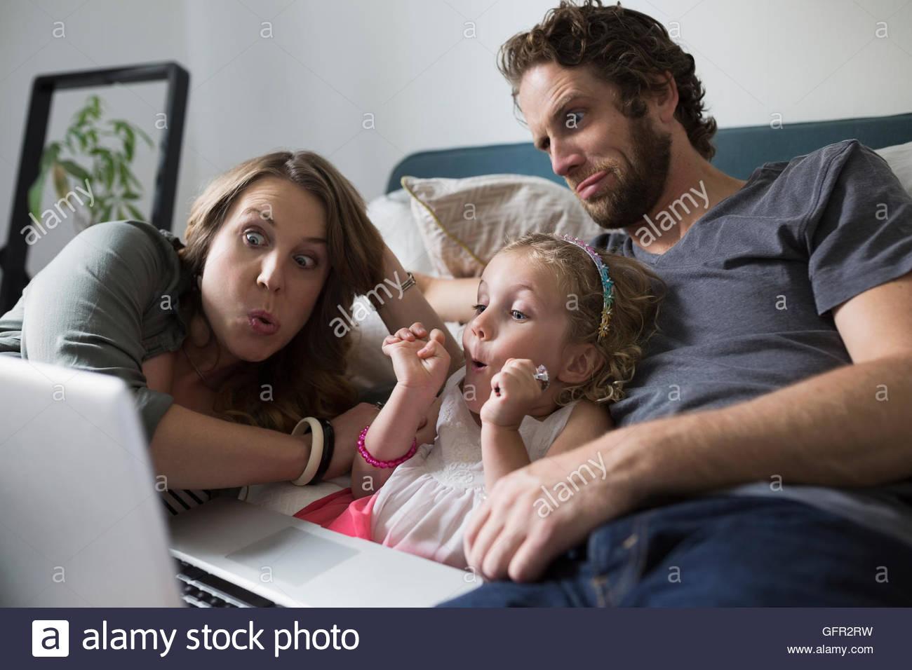 Famiglia giovane rendendo i volti della chat video con il computer portatile sul letto Immagini Stock