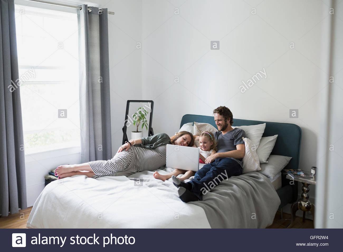 Giovane famiglia utilizzando laptop sul letto Immagini Stock