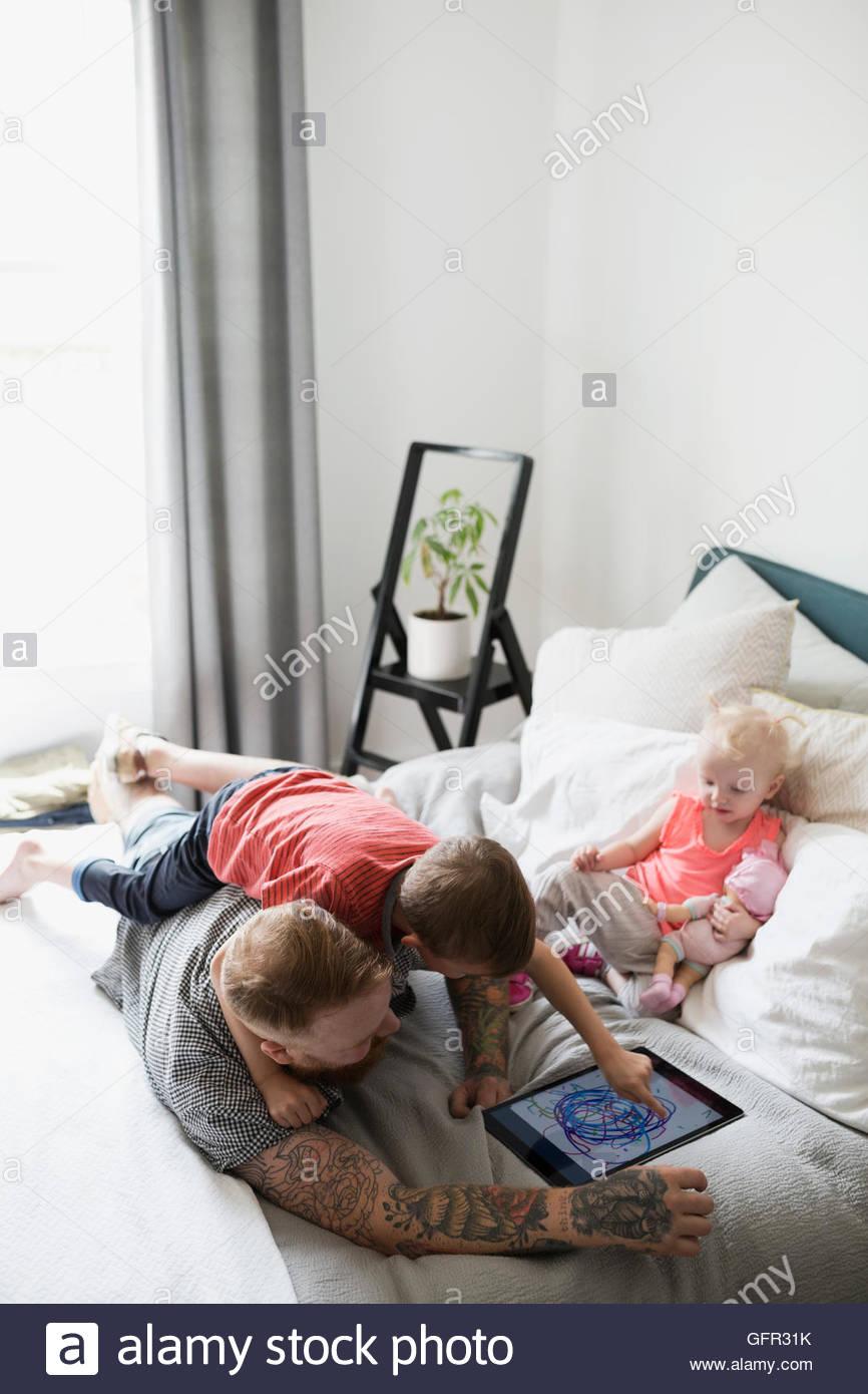 Padre e figli disegno sulla tavoletta digitale sul letto Immagini Stock