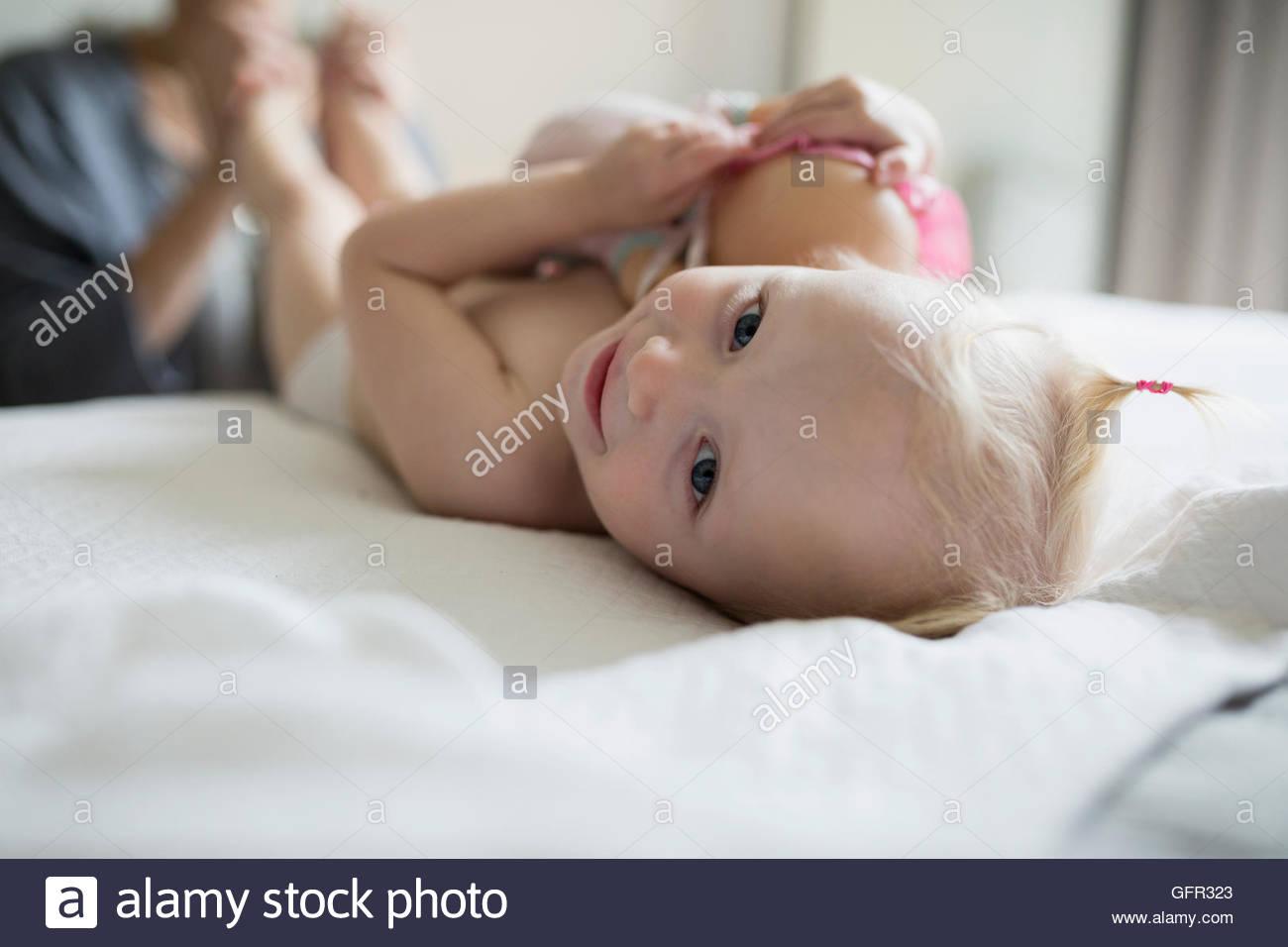 Close up ritratto sorridente bambina la posa sul letto con la bambola Immagini Stock